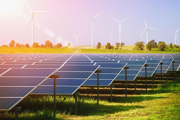 Panele słoneczne i turbiny wiatrowe wytwarzające energię elektryczną w elektrowni zielonej energii odnawialnej z niebieskim niebem. koncepcja ochrony zasobów naturalnych.