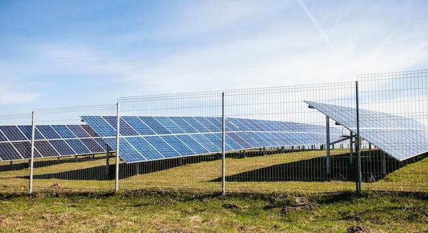 Panele słoneczne na tle górskiego krajobrazu i błękitnego nieba
