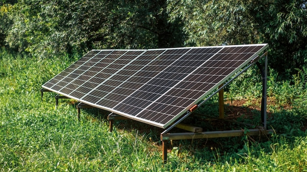 Panele słoneczne na ziemi w naturze. zieleń wokół
