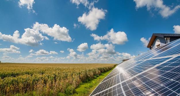 Panele słoneczne w pobliżu pola pszenicy i zachmurzone niebo