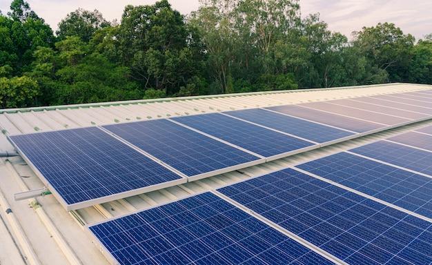 Panele słoneczne zainstalowane na dachu dużego budynku są pełne brudu i kurzu.