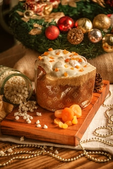 Panettone z białej czekolady z suszoną morelą na drewnianym stole z bombkami
