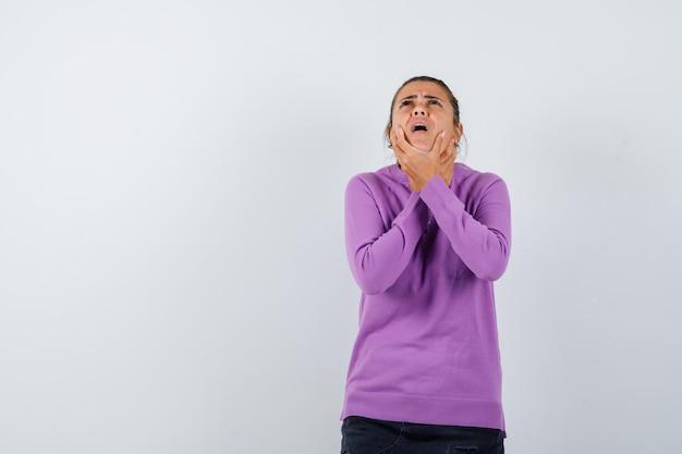 Pani cierpiąca na ból gardła w wełnianej bluzce i wyglądająca na chorą