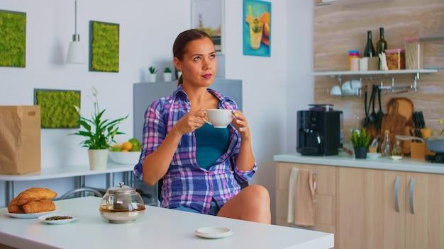 Pani ciesząca się gorącą zieloną herbatą popijając z porcelanowego kubka. kobieta pijąca stojąca przy stole w kuchni i patrząca przez szybę trzymająca filiżankę herbaty z naturalnym, aromatycznym napojem ziołowym.