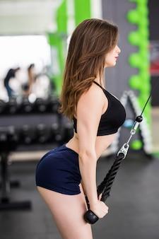 Pani fitness o silnym dopasowanym ciele wykonuje ćwiczenia ramion na siłowni z symulatorem sportowym