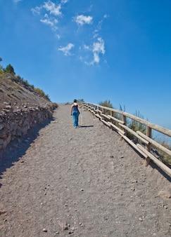 Pani idąca po ćwiczenia w słoneczny dzień na górskiej ścieżce