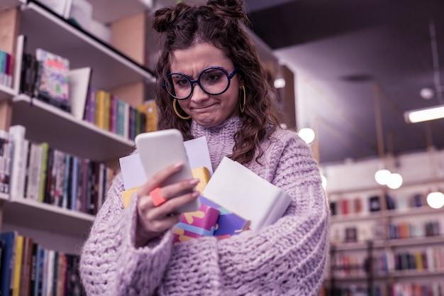 Pani jest zła. zdezorientowana ciemnowłosa dama niepewnie wpatrująca się w ekran smartfona, trzymając plik książek