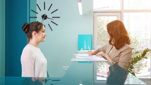 Pani kierownik biura w białej bluzce pokazuje książeczkę rejestracyjną klientce stojącej w recepcji we współczesnym szpitalu, widok z boku