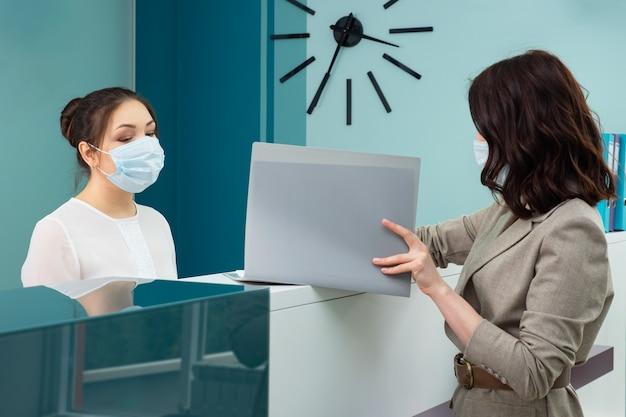 Pani kierownik biura z maską ochronną pokazuje książeczkę rejestracyjną klientce stojącej w recepcji we współczesnym szpitalu, widok z boku