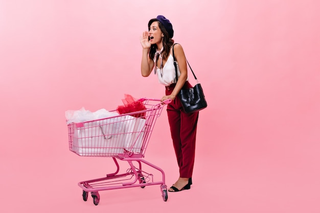 Pani krzyczy i niesie różowy wózek na zakupy. portret kobiety w czerwonych spodniach iz szalikiem na szyi iz czarną torbą na na białym tle.