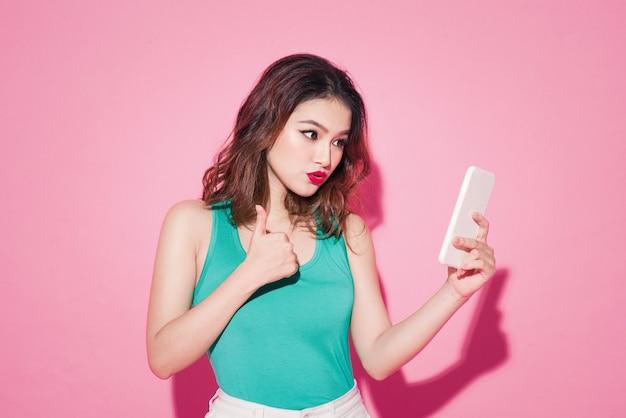 Pani lato. piękna azjatycka dziewczyna z profesjonalnym makijażem i stylową fryzurą biorąc selfie zdjęcie na różowym tle.
