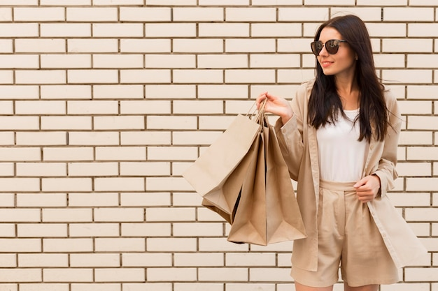 Pani moda trzymając torby na zakupy kopia przestrzeń mur ceglany