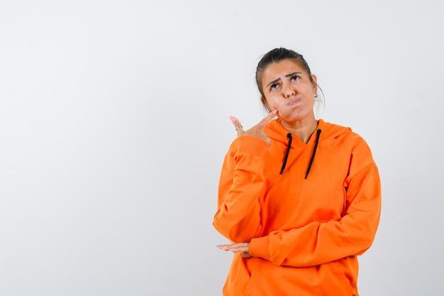 Pani naciskająca palcem na nadęty policzek w pomarańczowej bluzie z kapturem i patrząca z wahaniem