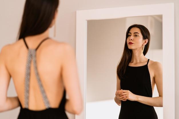 Pani nosi piękną czarną sukienkę, która patrzy w lustro