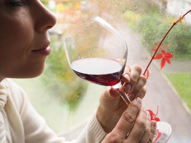 Pani pijąca wino przy oknie.