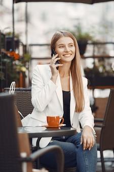 Pani pije kawę. kobieta siedząca przy stole. dziewczyna używa telefonu.