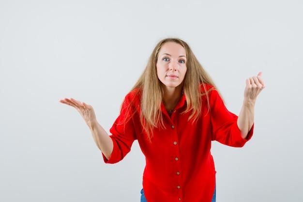 Pani pokazująca bezradny gest w czerwonej koszuli i wyglądająca na zdezorientowaną,