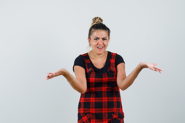 Pani pokazująca bezradny gest w fartuszku i wyglądająca na zdezorientowaną. przedni widok.