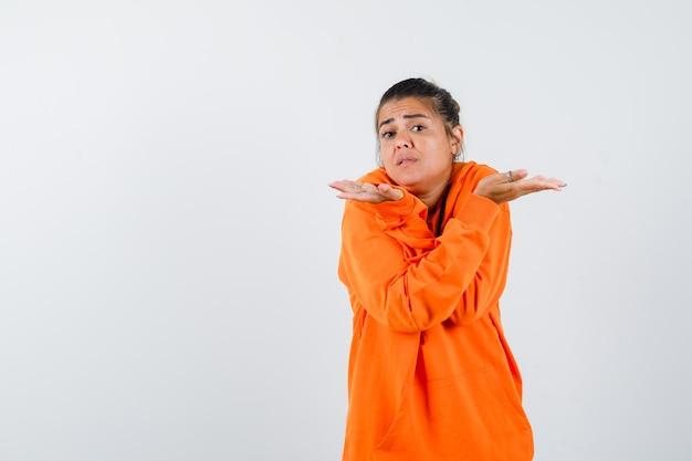 Pani pokazująca bezradny gest w pomarańczowej bluzie i wyglądająca na zdezorientowaną