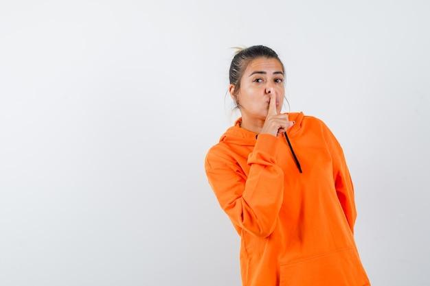 Pani pokazująca gest ciszy w pomarańczowej bluzie z kapturem i wyglądająca rozsądnie