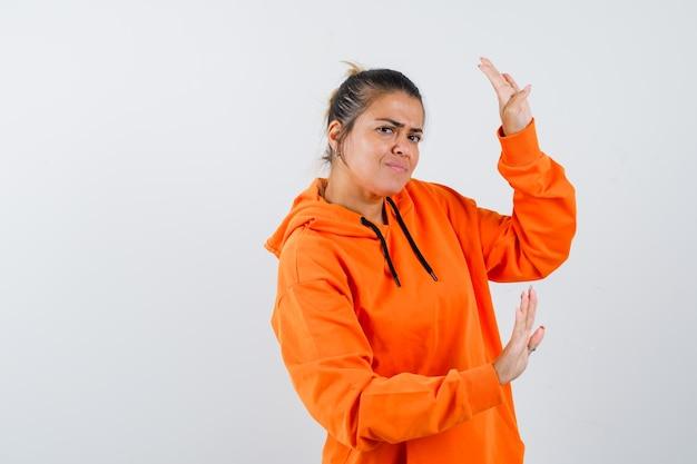 Pani pokazująca gest zatrzymania w pomarańczowej bluzie z kapturem i wyglądająca na przestraszoną