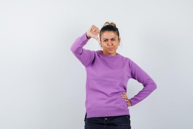 Pani pokazująca kciuk w dół w wełnianej bluzce i wyglądająca na niezadowoloną