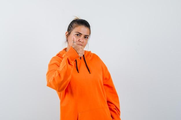 Pani pokazująca kciuk w pomarańczowej bluzie z kapturem i wyglądająca na pewną siebie