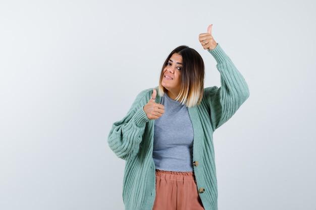Pani pokazująca podwójne kciuki do góry w zwykłym ubraniu i wyglądająca na szczęśliwą. przedni widok.
