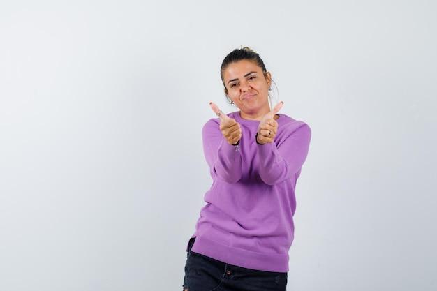 Pani pokazująca podwójne kciuki w wełnianej bluzce i wyglądająca na pewną siebie