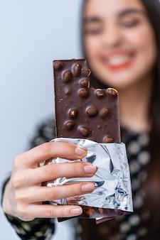 Pani pokazuje batonik czekoladowy z orzechami do kamery. koncepcja słodkiego życia.