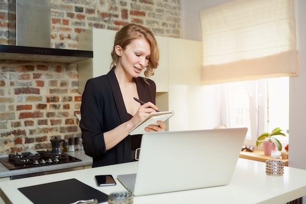 Pani pracuje zdalnie na laptopie w kuchni. dziewczyna z uśmiechem robi notatki do notesu podczas raportu kolegi z wideokonferencji w domu.