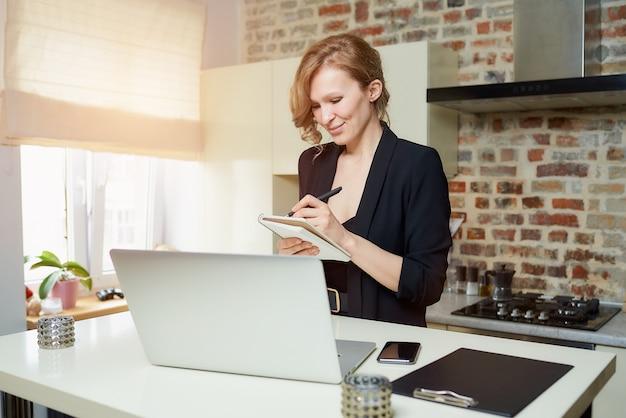 Pani pracuje zdalnie na laptopie w kuchni. szczęśliwa dziewczyna robi notatki do notesu podczas raportu kolegi z wideokonferencji w domu ..