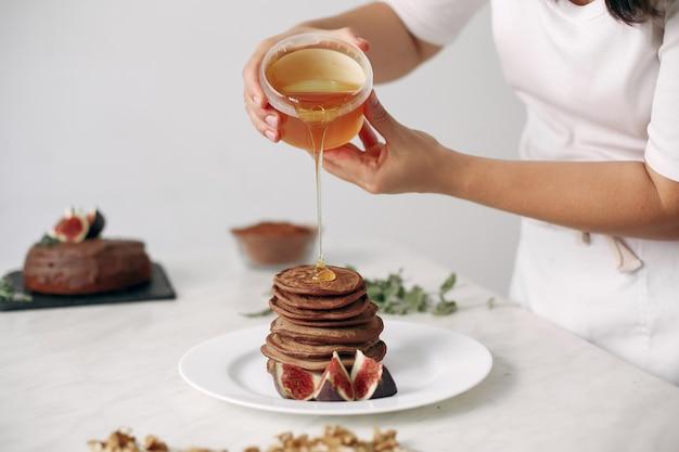 Pani przygotowuje deser. cukiernik piecze naleśniki kobieta gotowała jedzenie.