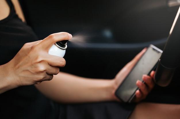 Pani stosująca środek dezynfekujący do telefonów komórkowych w celu ochrony przed wirusem koronowym. regularne warunki sanitarne zapobiegają rozprzestrzenianiu się wirusa.