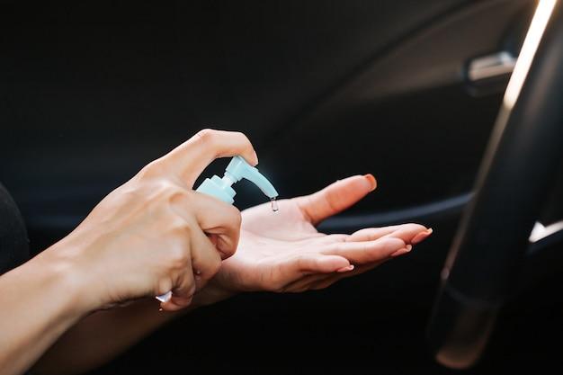 Pani stosująca żelowy środek dezynfekujący na smartfonie zapobiega rozprzestrzenianiu się wirusa korony. regularne warunki sanitarne zapewniają bezpieczeństwo przed wirusem.