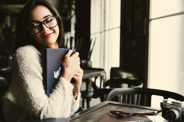 Pani trzyma stare fotoalbumy czule siedzą w kawiarni