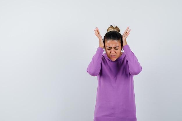 Pani trzymająca ręce na głowie w wełnianej bluzce i wyglądająca na zirytowaną