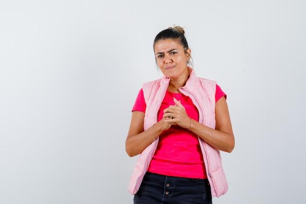 Pani trzymająca ręce splecione w koszulkę, kamizelkę i wyglądająca na zamyśloną