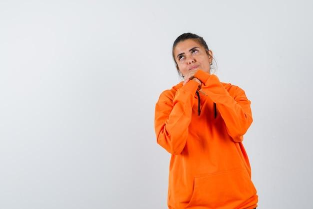 Pani trzymająca się za ręce splecione w pomarańczową bluzę z kapturem i wyglądająca na marzycielską