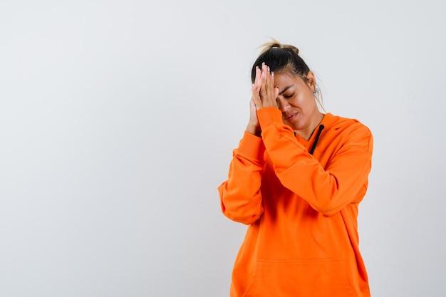 Pani trzymająca się za ręce w geście modlitwy w pomarańczowej bluzie z kapturem i patrząca z nadzieją