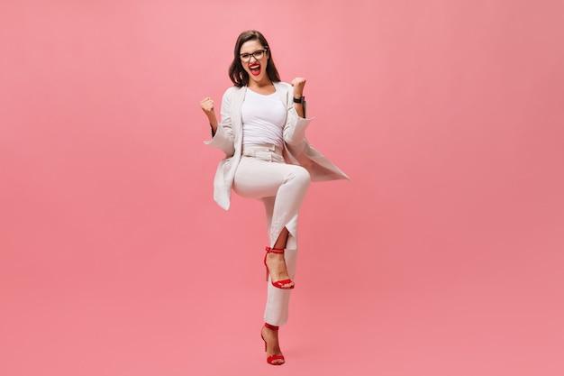 Pani w beżowym stroju emocjonalnie pozuje na na białym tle. jasna dziewczyna w okularach iz czerwoną szminką bawi się i śmieje z kamery.