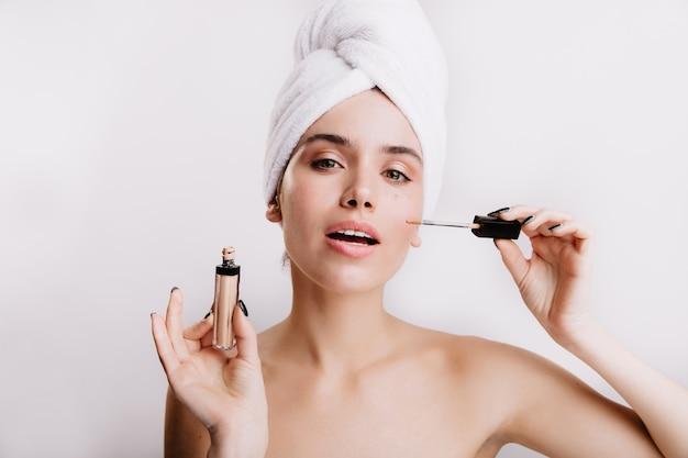 Pani w białym ręczniku na głowie wykonuje makijaż nago za pomocą korektora. szczegół portret zielonookiej dziewczyny na odizolowanej ścianie.