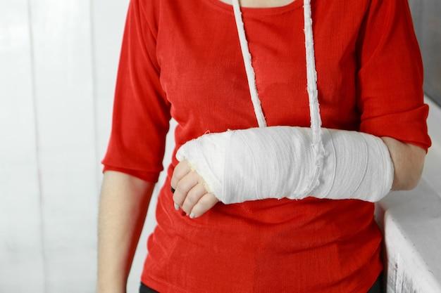 Pani w czerwonej kurtce ze złamaną ręką