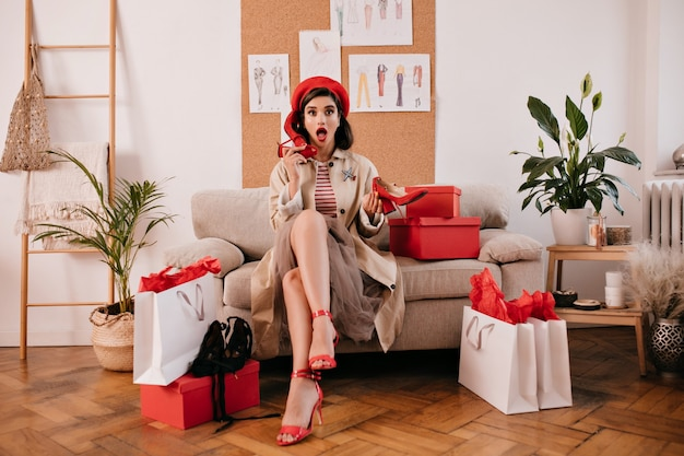 Pani w czerwonym berecie i modnym płaszczu trzyma szpilki. ładna kobieta w czerwonym berecie i swetrze w paski, pozowanie na beżowej wygodnej kanapie.