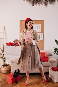 Pani w czerwonym kapeluszu i płaszczu pozuje z torbą na zakupy. piękna dziewczyna z jasnymi ustami w długiej spódnicy, na wysokich obcasach i swetrze w paski uśmiecha się.