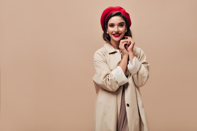 Pani w dobrym nastroju patrzy w kamerę na beżowym tle. piękna uśmiechnięta kobieta z dużymi, jasnymi ustami w czerwonym berecie, w kolczyki i pozowanie długi płaszcz.