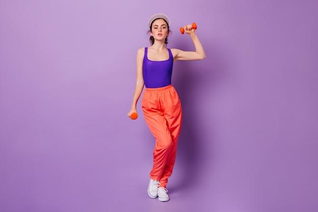 Pani w fioletowym sportowym topie i pomarańczowych spodniach robi ćwiczenia na ręce z czerwonymi hantlami