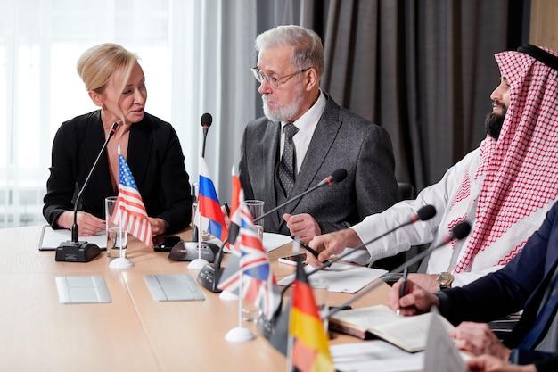Pani w garniturze słuchająca dyskusji przywódcy politycznego, siedząca przy biurku w sali konferencyjnej, współpracująca. spotkanie bez krawatów, koncepcja biznesowa