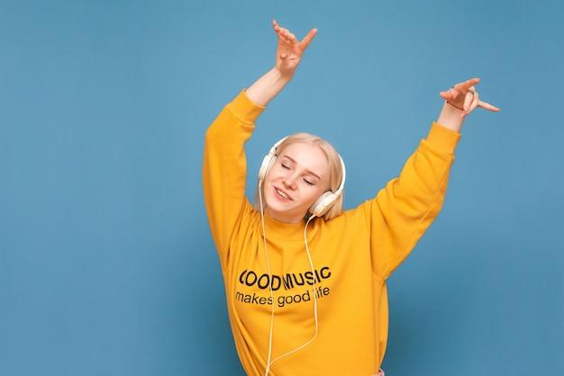Pani w jaskrawym, ulicznym ubraniu słucha muzyki w słuchawkach z zamkniętymi oczami i tańczy na niebiesko