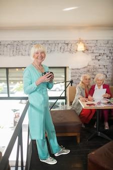 Pani w kolorze niebieskim. blondynka w niebieskim garniturze stojąca z filiżanką herbaty w dłoniach i uśmiechnięta